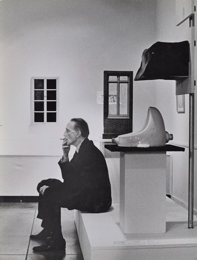 Duchamp smoking in front of Fountain, Duchamp Retrospective, Pasadena Art Museum