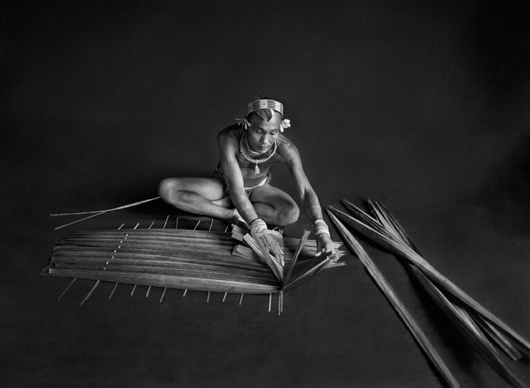 Teureum, sikeirei (shaman), leader of the Mentawai clan, prepasring a filter for sago. Siberut Islansd.
