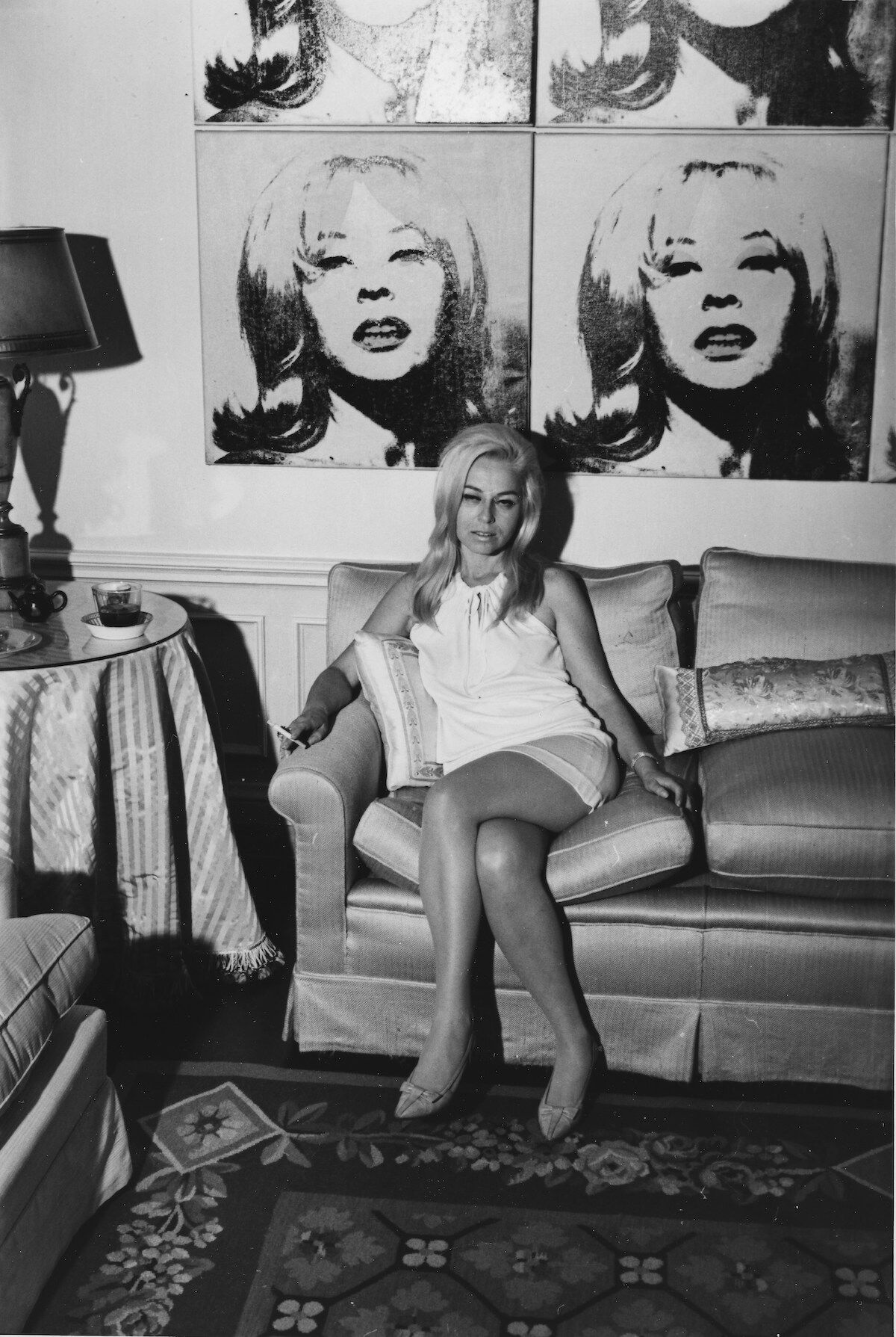 Portrait of Holly Solomon at home with Andy Warhol portrait circa 1966. Courtesy of Thomas Solomon.
