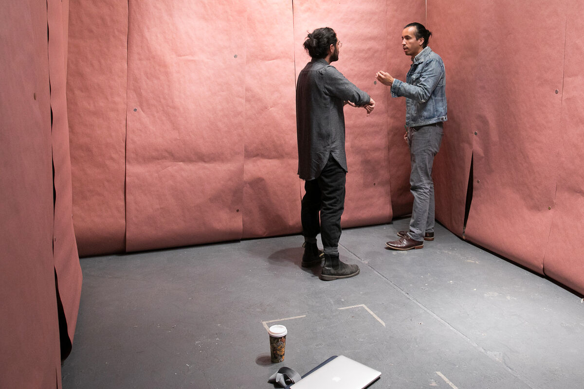 Artist Rodrigo Valenzuela works with a student during an open studio at UCLA. Photo by Reed Hutchinson. Courtesy of UCLA.