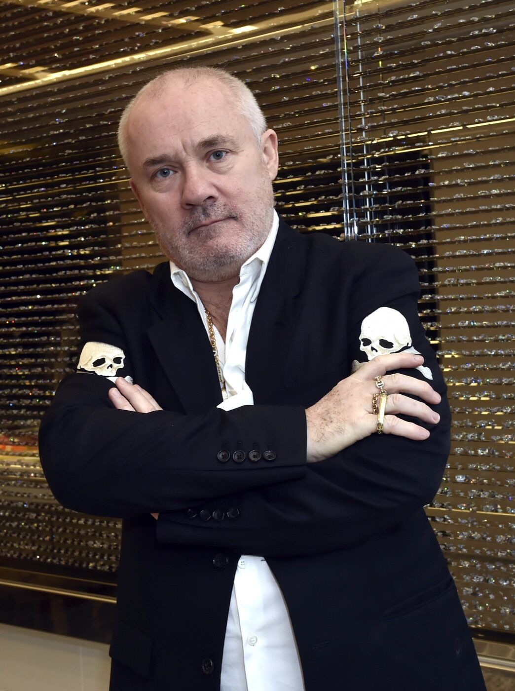 Portrait of Damien Hirst in front of his work The Winner Takes It All, 2018 in the Empathy Suite at Palms Casino Resort, Las Vegas. Image courtesy of Palms Casino Resort.
