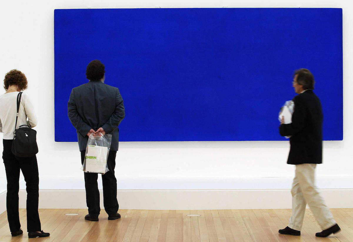 Visitors look at an Yves Klein painting at the Schirn Kunsthalle in Frankfurt. Photo by Thomas Lohnes/AFP/Getty Images.