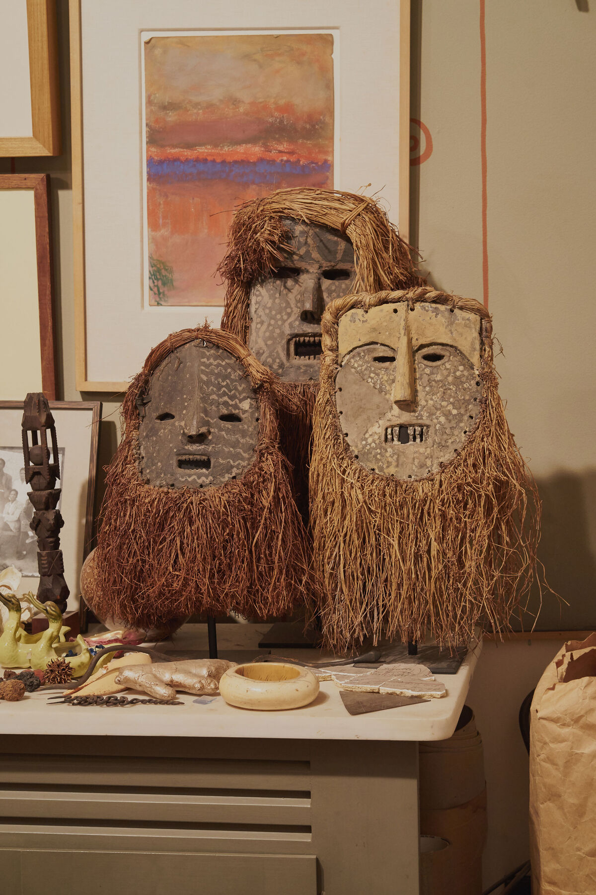 Three masks by Ndaaka artists from the Ituri Rainforest in the Democratic Republic of the Congo greet dinner guests at Fagaly. Behind them, a pastel by Charles Woodward Hutson hangs on the wall, a self-taught artist who lived and worked in New Orleans. Photo by Michael Adno for Artsy.