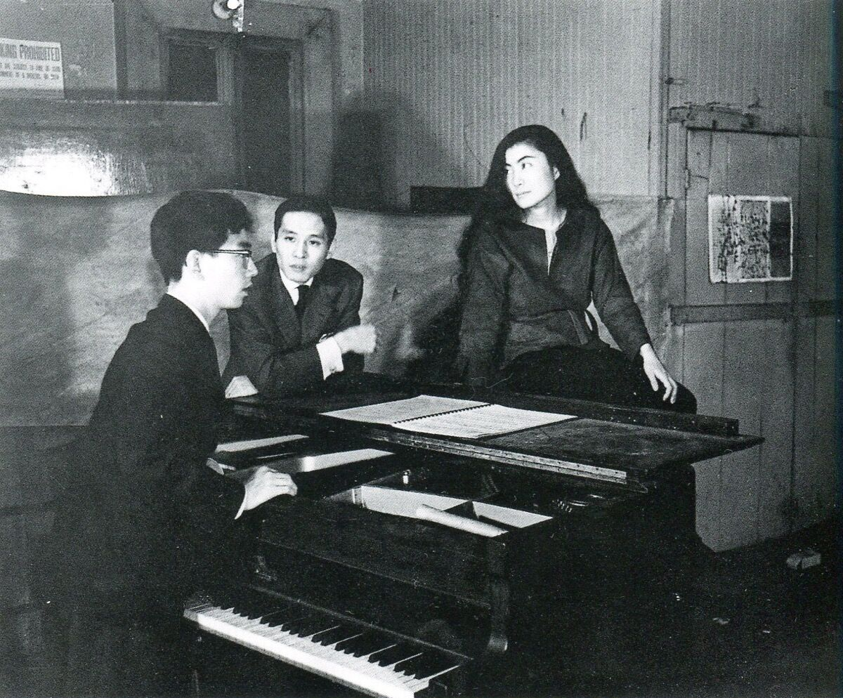 Yoko Ono with Toshi Ichiyanagi (at the piano) and Toshiro Mayuzumi at her Chambers Street loft, 1961. Photograph: Minoru Niizuma. Collection of Yoko Ono, New York. © Yoko Ono. Image courtesy of Grey Art Gallery.