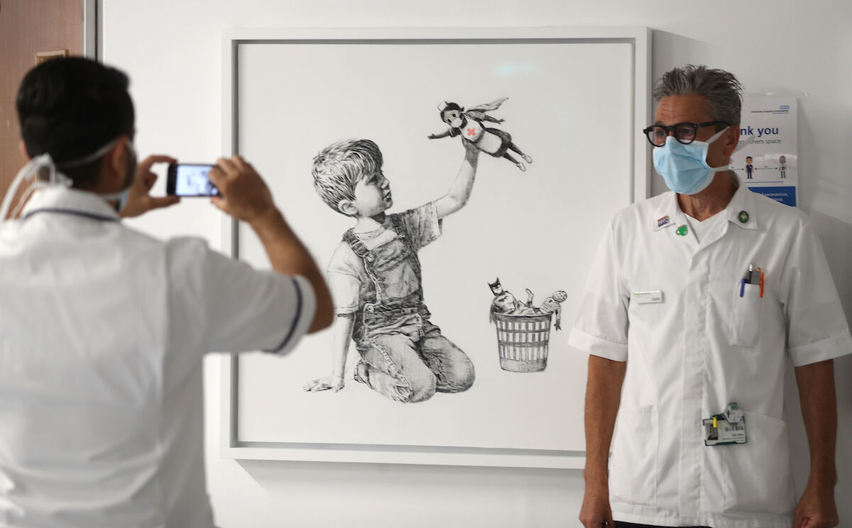 A member of staff has their photograph taken in front of a new artwork painted by Banksy that has gone on display to staff and patients on Level C of Southampton General Hospital. Photo by Andrew Matthews/PA Images via Getty Images.