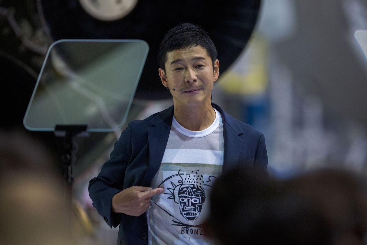 Japanese billionaire Yusaku Maezawa wears a shirt depicting a work by Jean-Michel Basquiat during the announcement by Elon Musk that he will be the first private passenger who will fly around the Moon aboard the SpaceX BFR launch vehicle. Photo by David McNew/AFP/Getty Images.