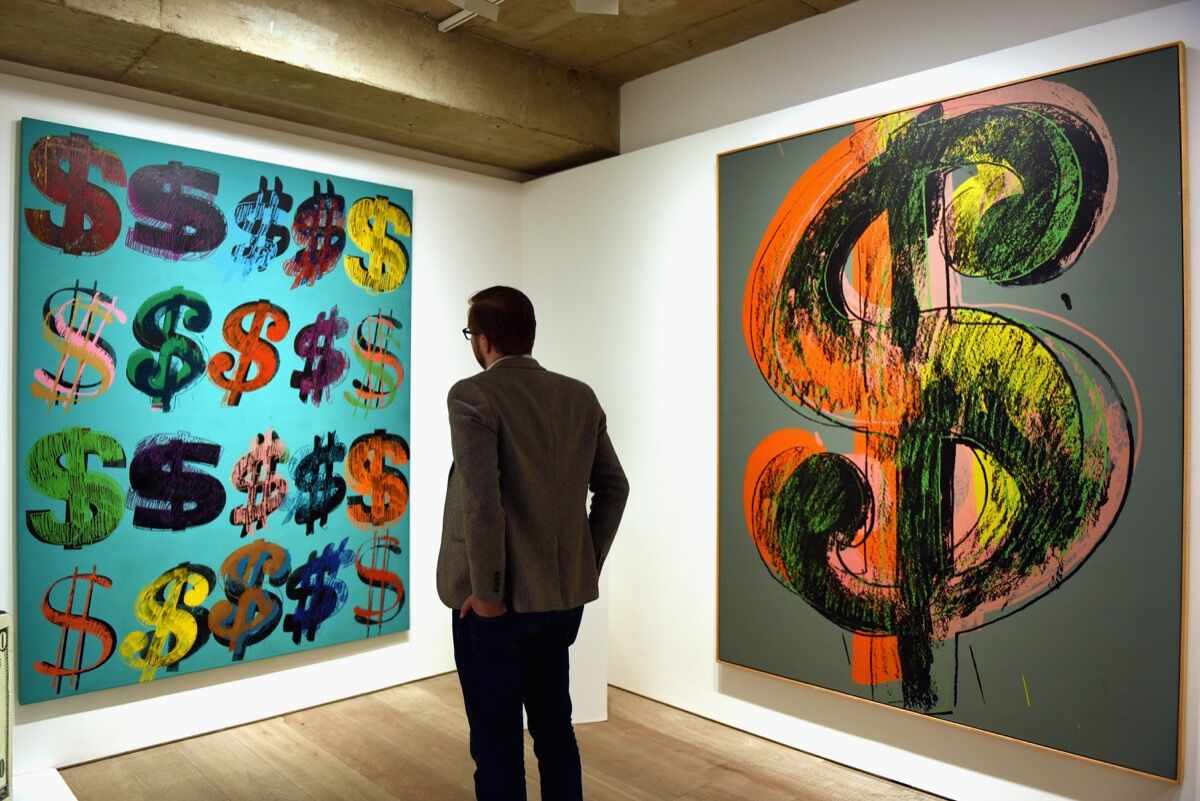 A visitor studies Andy Warhol, Dollar Signs, 1981, at Sotheby's, London in 2015. Photo by Mary Turner/Getty Images.