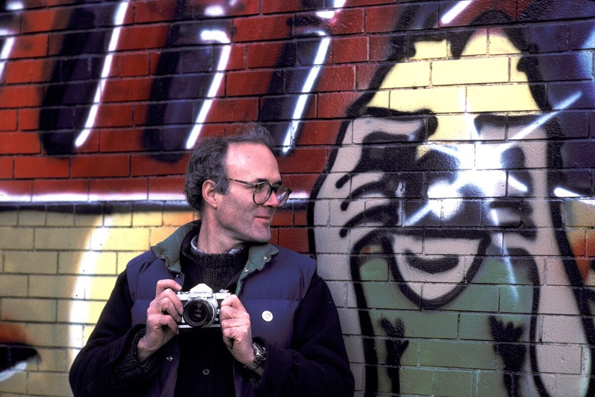 Henry Chalfant next to his portraitnon the set of Style Wars. Photo © Martha Cooper 1982.
