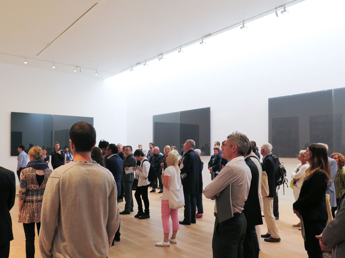 Installation view of Gerhard Richter's paintings, including choir members performing Arvo Pärt's composition. Photo: Jan Chlebik.