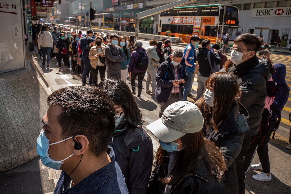 Residents wait to buy face masks from a Hong Kong pharmacy. Photo by Anthony Kwan/Getty Images.