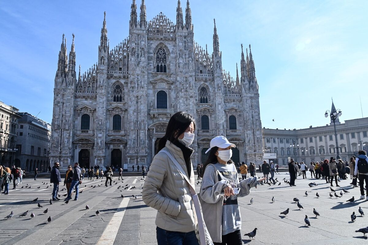 Two women wearing face masks pass the Duomo in Milan on February 24, 2020. Photo by Andreas Solaro/AFP via Getty Images.