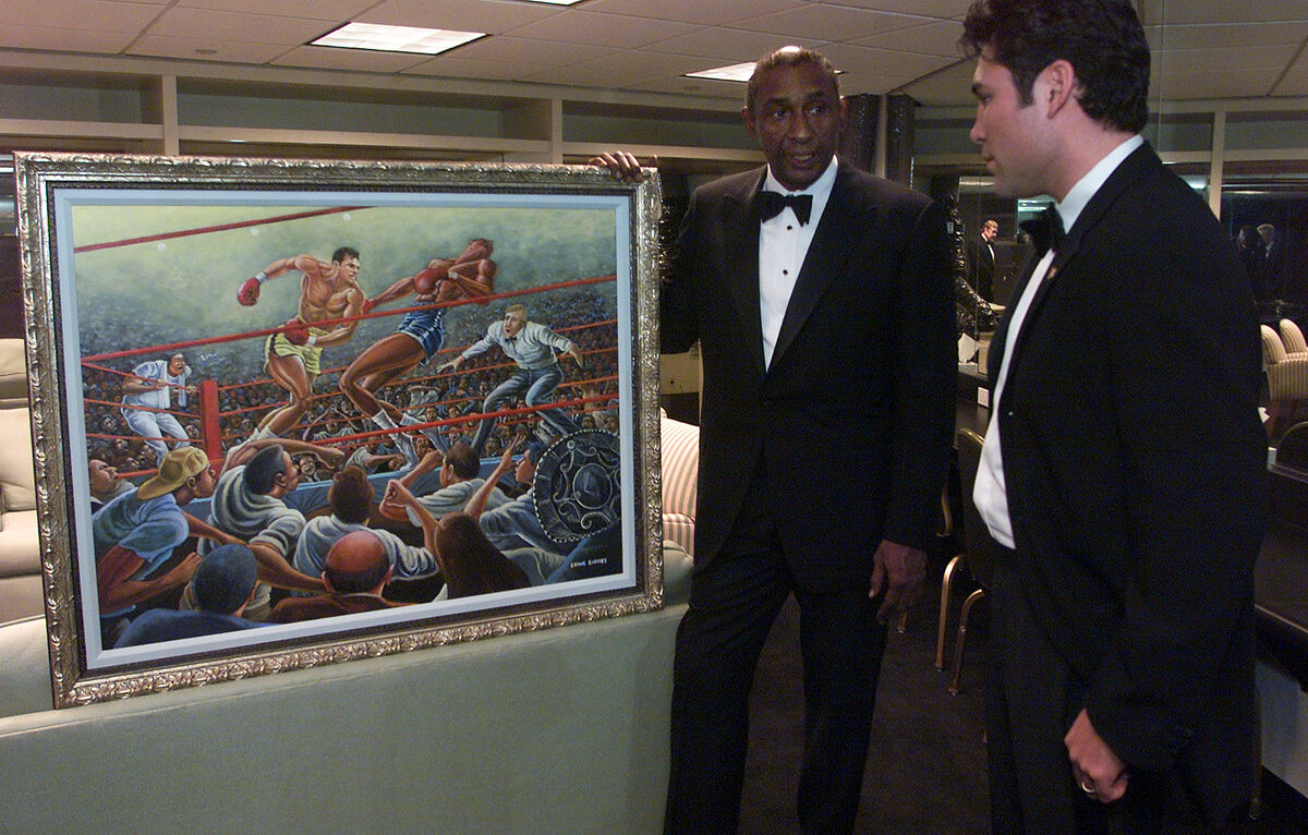 Ernie Barnes shows a painting of Oscar De La Hoya, commissioned by Jerry Buss, to De La Hoya at the Beverly Hilton. Photo by George Wilhelm/Los Angeles Times. Image via Getty Images.