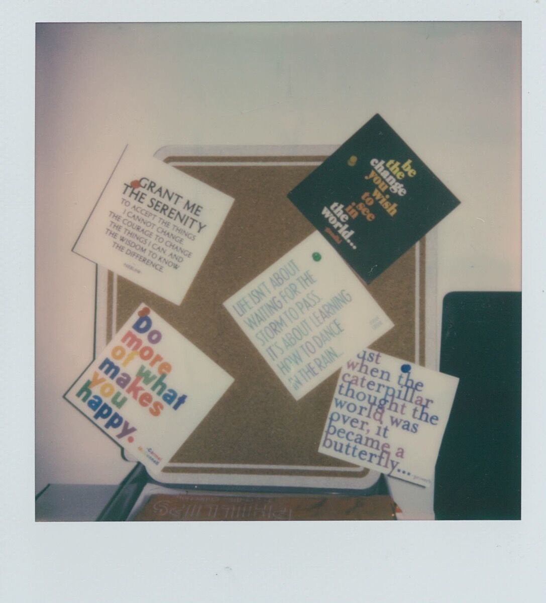 """Cheerful postcards pinned to a small pinboard above Clay's desk feature positive affirmations: """"Be the change you wish to see…,"""" """"Grant me the serenity…."""""""