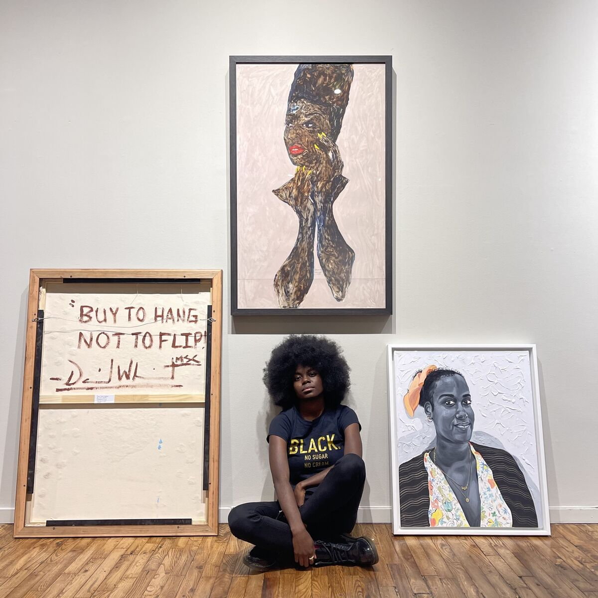 """Portrait of Destinee Ross-Sutton with, from left to right, works by David """"Mr. StarCity"""" White (showing the back of the work), Amoako Boafo, and Otis Kwame Kye Quaicoe, from the exhibition """"Black Voices: Friend of My Mind."""" Courtesy of Destinee Ross-Sutton."""