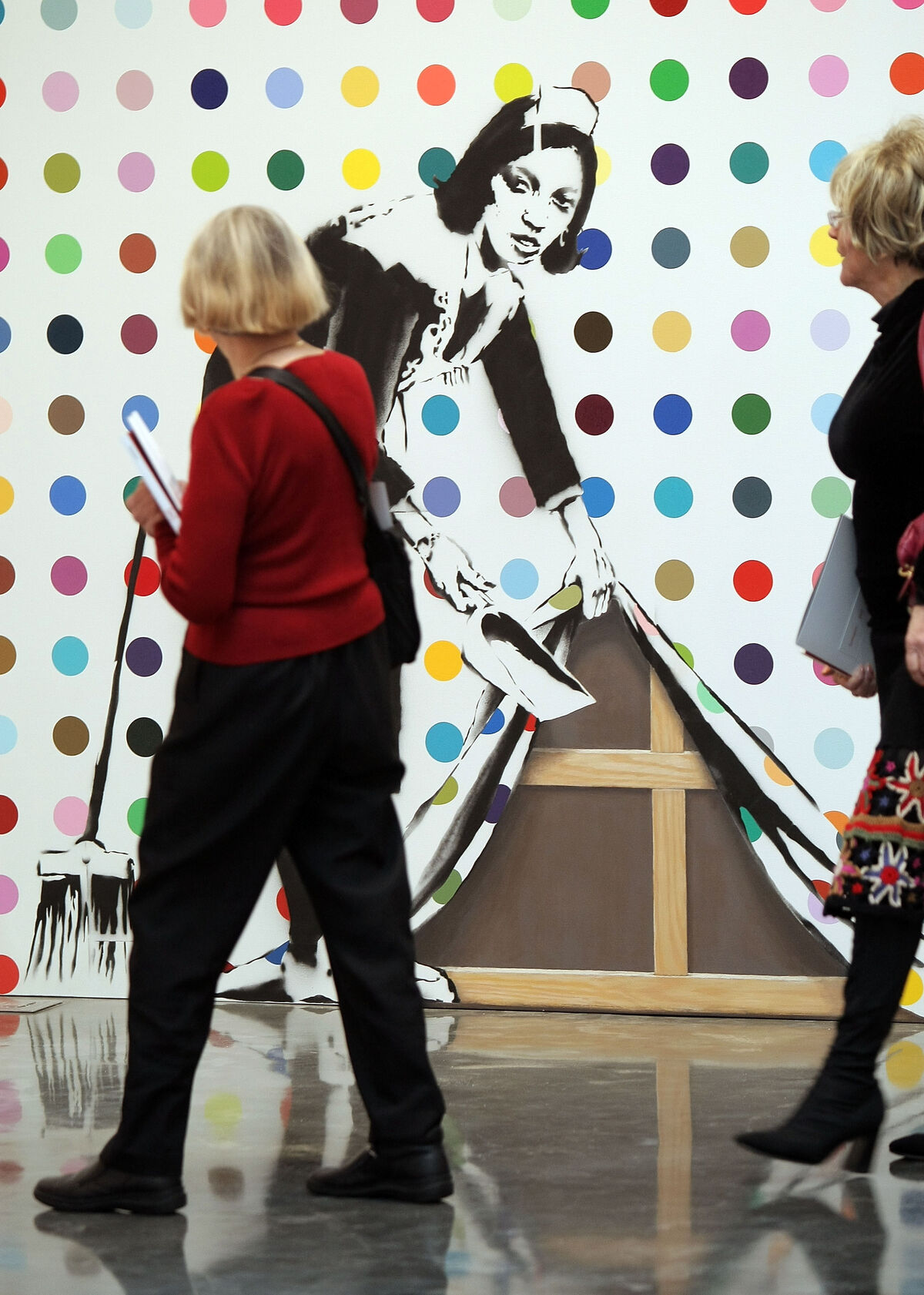 Guests look at a painting by Banksy at the (RED) Auction, Gagosian Gallery, 2008. Photo by Scott Gries via Getty Images.