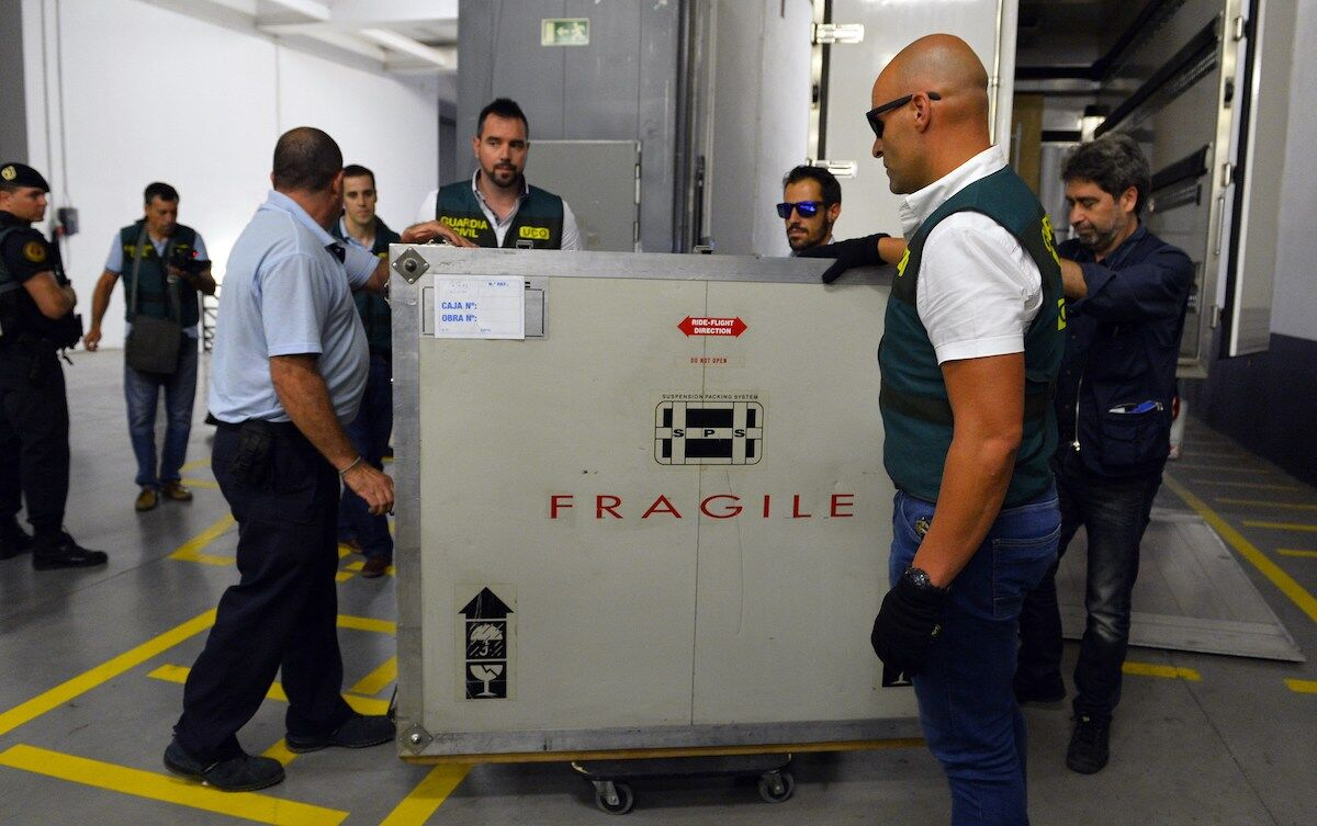 Spanish Civil Guards unload a box containing the Picasso painting Head of a Young Woman at the Reina Sofia museum in Madrid. Photo by Gerard Julien/AFP via Getty Images.