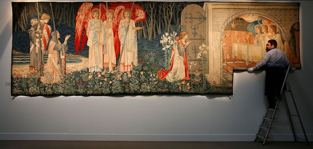 A Sotheby's technician attends to The Attainment: The Vision of the Holy Grail to Sir Galahad, Sir Bors and Sir Perceval, a tapestry designed by Edward Burne-Jones and woven at the workshop of Morris & Co, on March 14, 2008. The tapestry has been in the collection of Led Zeppelin's Jimmy Page since 1978. Photo by Cate Gillon/Getty Images.
