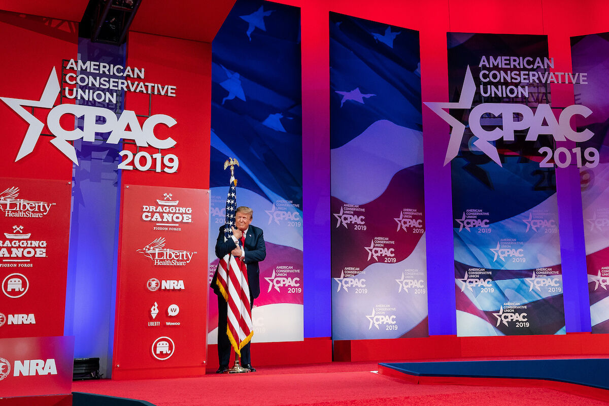 U.S. President Donald Trump hugged a U.S. flag at the Conservative Political Action Conference on March 2, 2019. Photo by Official White House Photo by Tia Dufour, via Flickr.