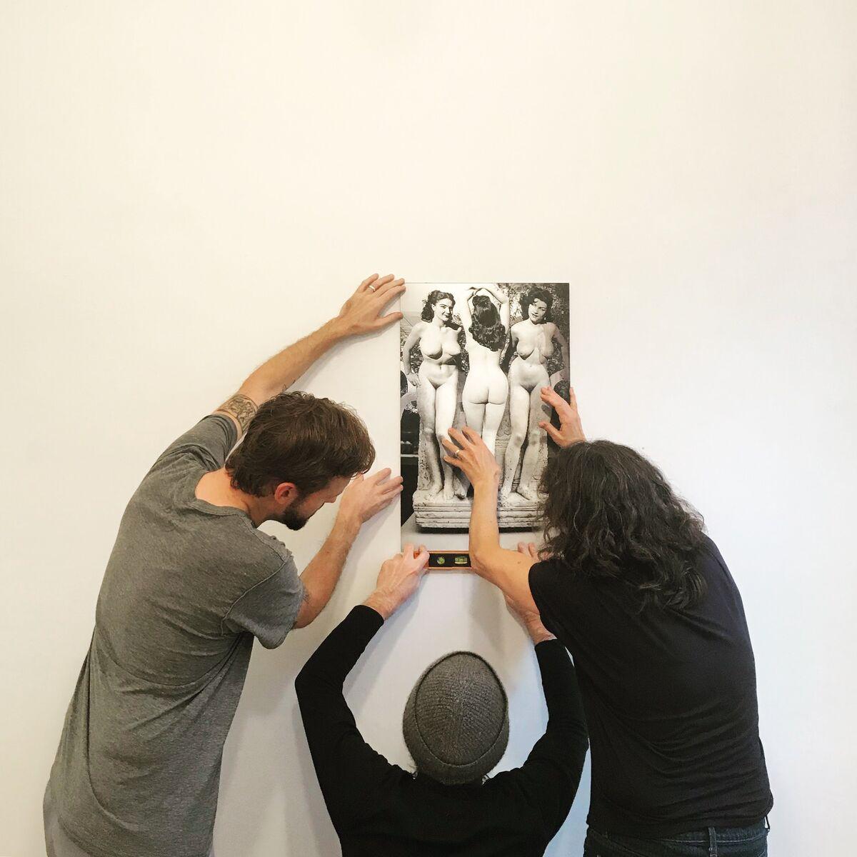 Scott Indrisek, John Miller, and Aura Rosenberg install a lenticular work by Rosenberg at Teen Party. Courtesy of Teen Party.