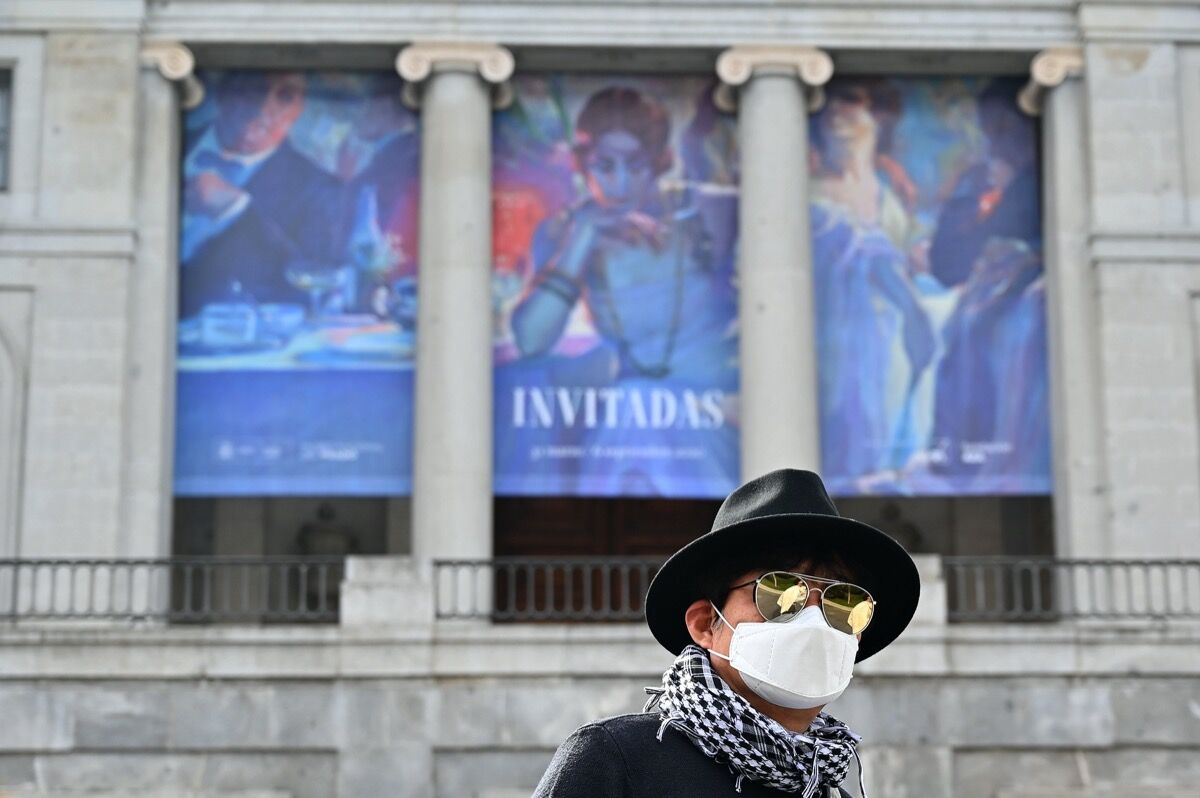 A man wearing a protective face mask walks in front of El Prado museum in Madrid on March 12, 2020, after all of Madrid's state-run museums were closed to the public due to the coronavirus outbreak. Photo by Gabriel Bouys / AFP via Getty Images.
