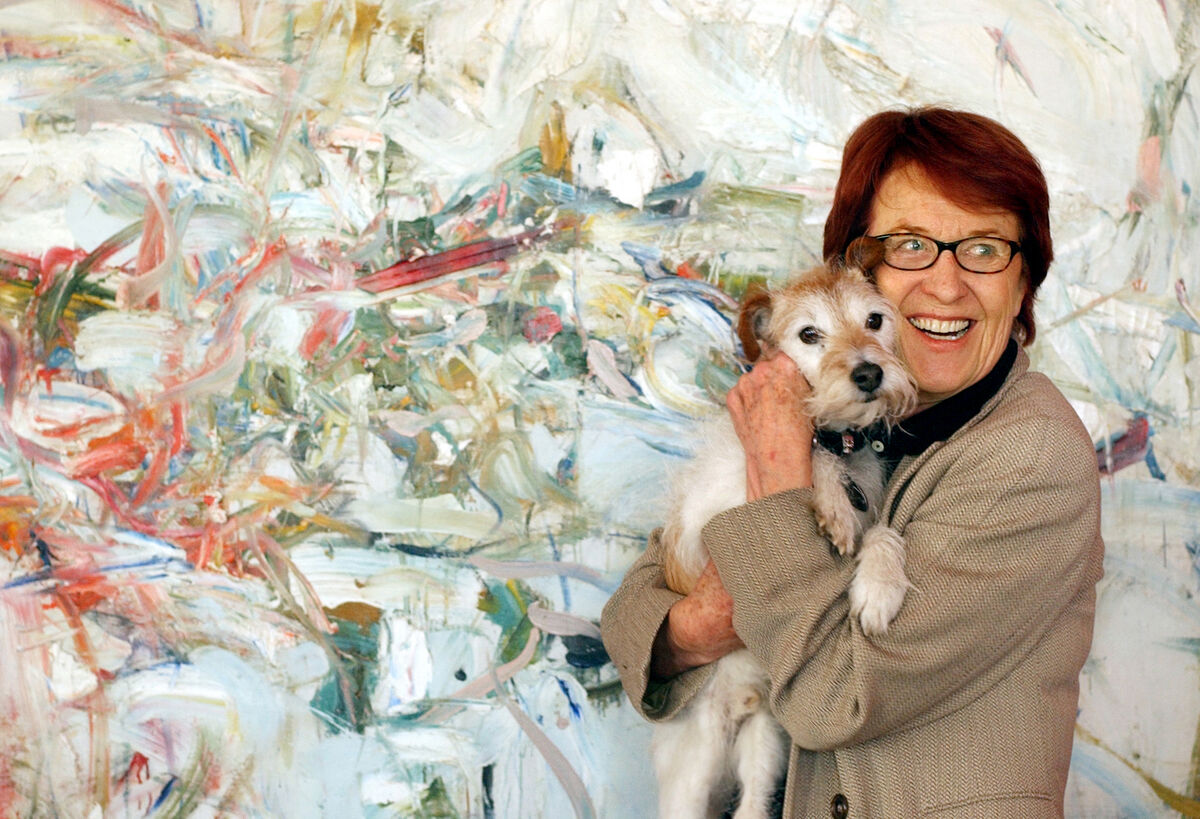 Portrait of Ginny Williams with her pooch, Willie, in front of a Joan Mitchell painting. Photo By Karl Gehring for The Denver Post. Image via Getty Images.