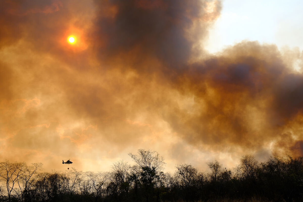 A helicopter flies over forest fires in Santa Cruz, Bolivia. Photo by Adolfo Lino/picture alliance, via Getty.