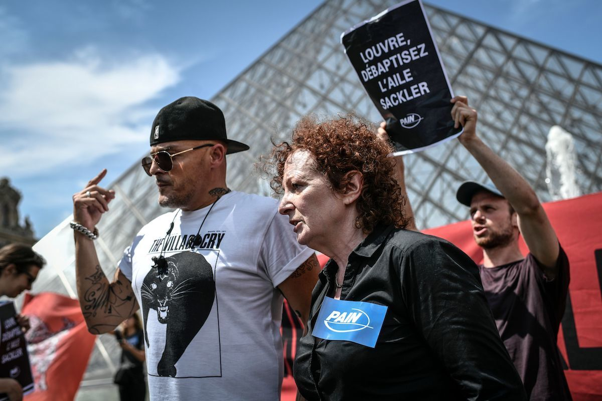 Nan Goldin, artist and founder of PAIN, with the mission head of AIDES, Fred Bladou, during an anti-Sackler protest at the Louvre. Photo by Stephane de Sakutin/AFP/Getty Images.