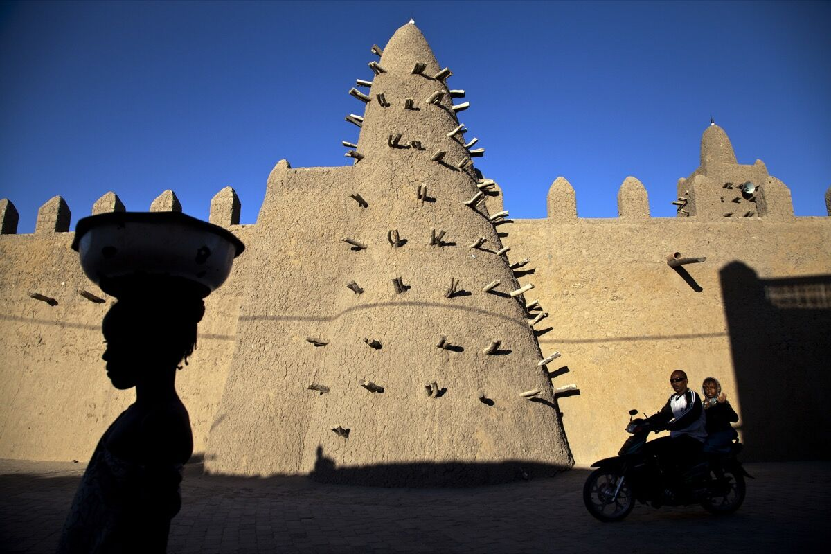 Residents of Timbuktu pass by Djingareyber Mosque, one of the historical architectural structures (along with Sankore Mosque, Sidi Yahia Mosque and sixteen mausoleums and holy public places) which together earned Timbuktu the designation of World Heritage Site by UNESCO. UN Photo/Marco Dormino, via Flickr.