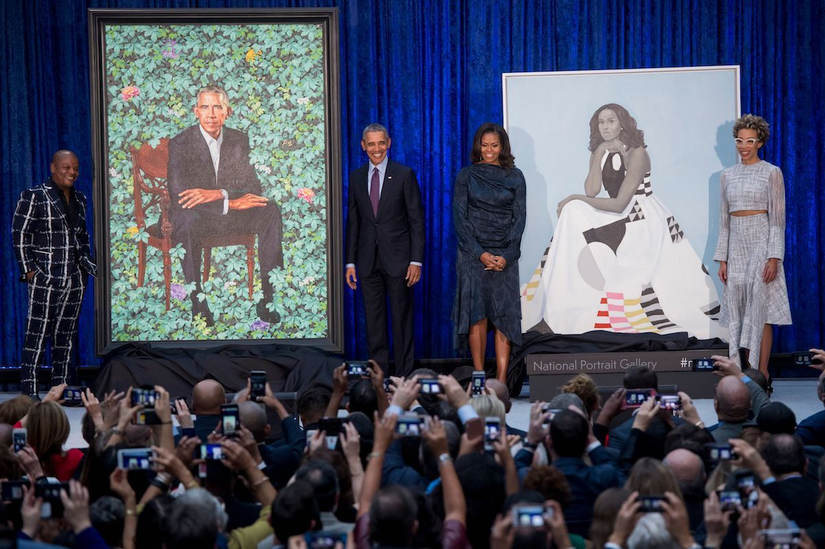 Barack and Michelle Obama pose with Kehinde Wiley and Amy Sherald, and the artists' portraits of the former U.S. president and first lady during a ceremony at the National Portrait Gallery on February 12, 2018. Photo by Saul Loeb/AFP via Getty Images.