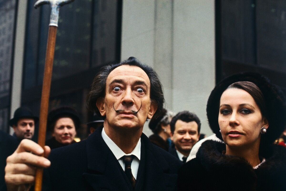 Artist Salvador Dali, lifting his cane, in a crowd. Image via Getty Images.