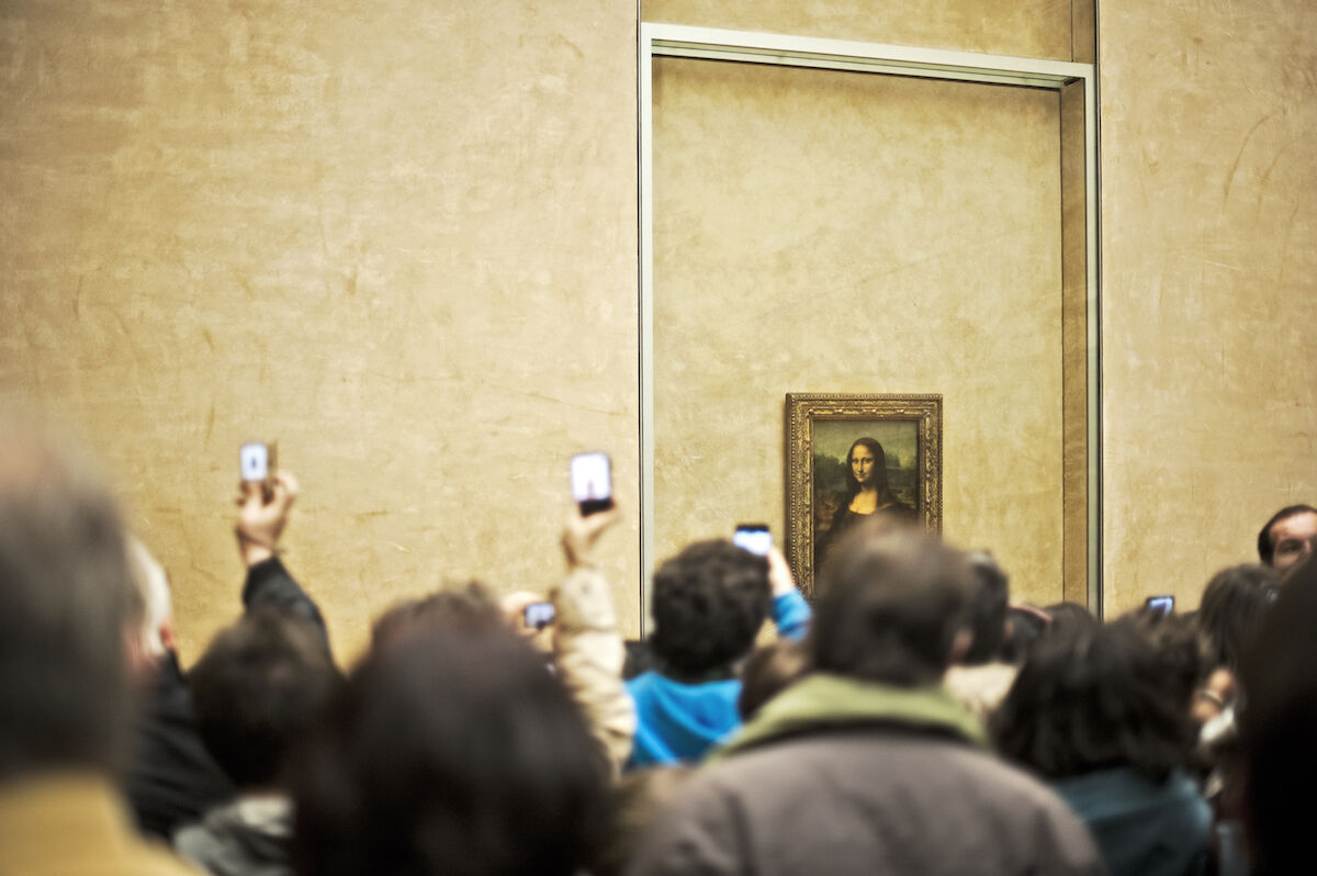 Crowds surround the Mona Lisa (ca. 1503–18) by Leonardo da Vinci at the Louvre. Photo by Michael Haase, via Wikimedia Commons.