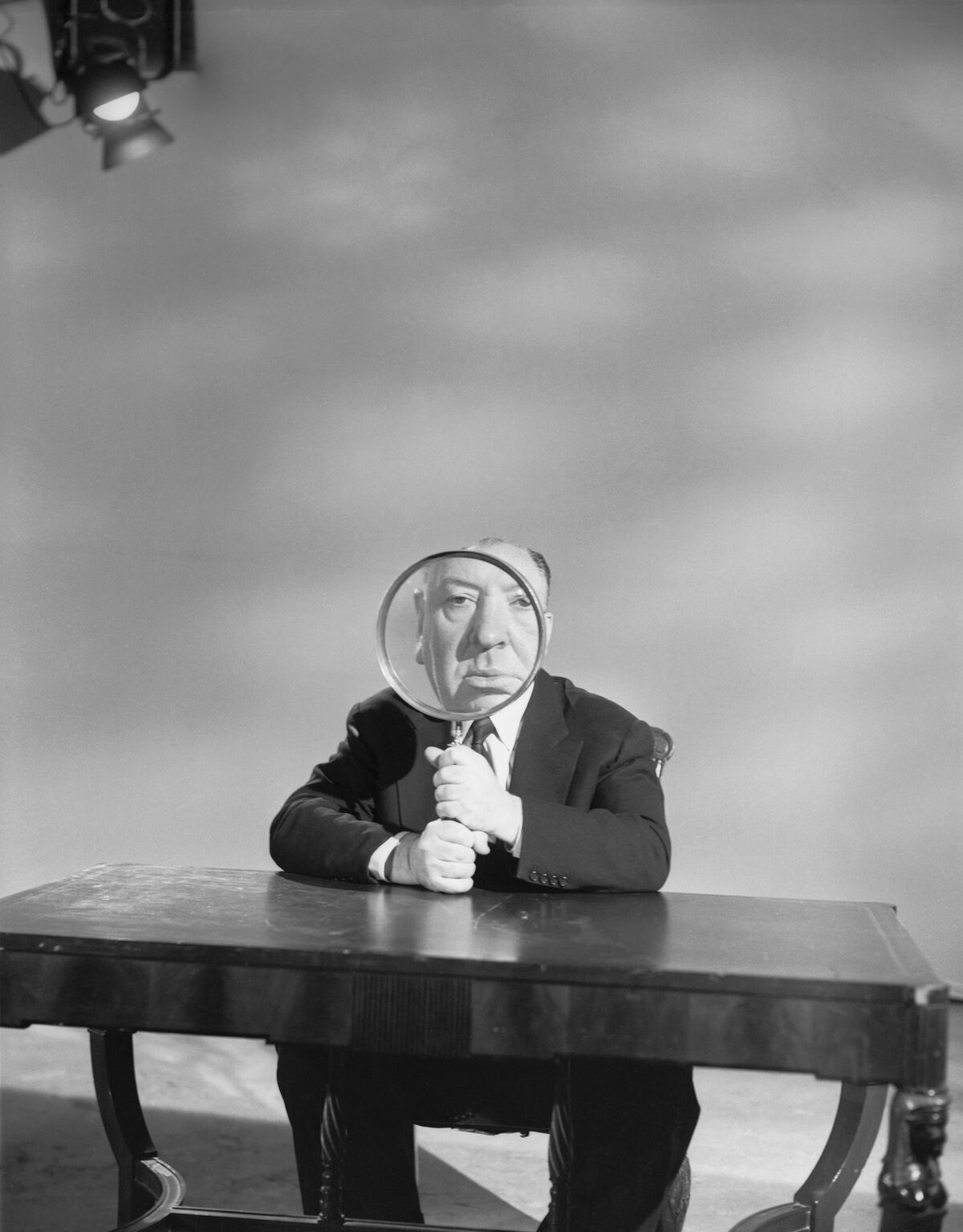 Alfred Hitchcock plays with a magnifying glass on the set of his television show Alfred Hitchcock Presents, 1956. Photo by Bettmann/Getty Images.