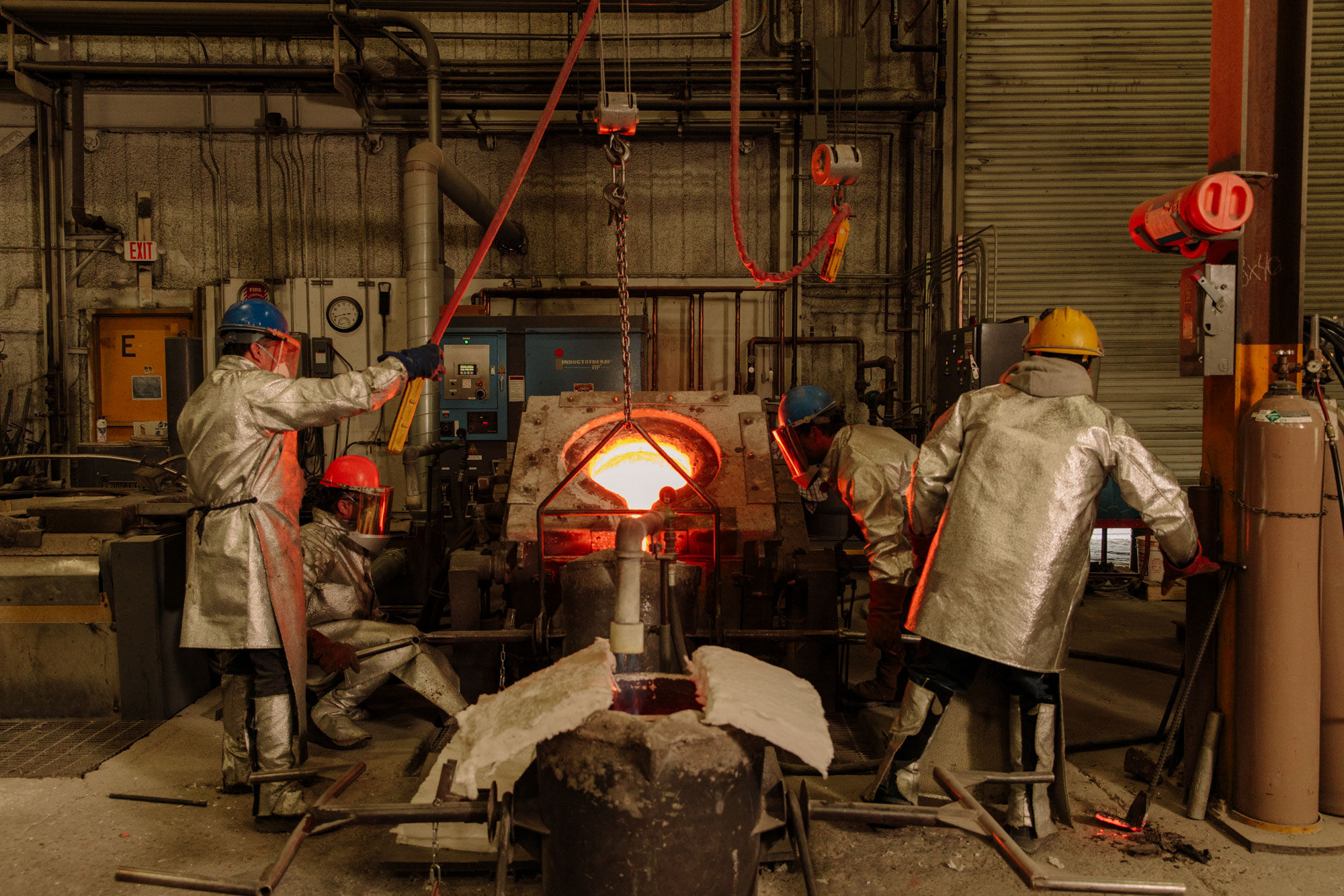 PTX foundrymen pouring molten metal into a crucible. Photo by Ricky Rhodes for Artsy.