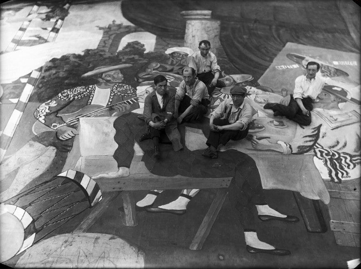 Pablo Picasso, (wearing a beret) and scene painters sitting on the front cloth for Léonide Massine's ballet Parade, 1917. Image via Wikimedia Commons.