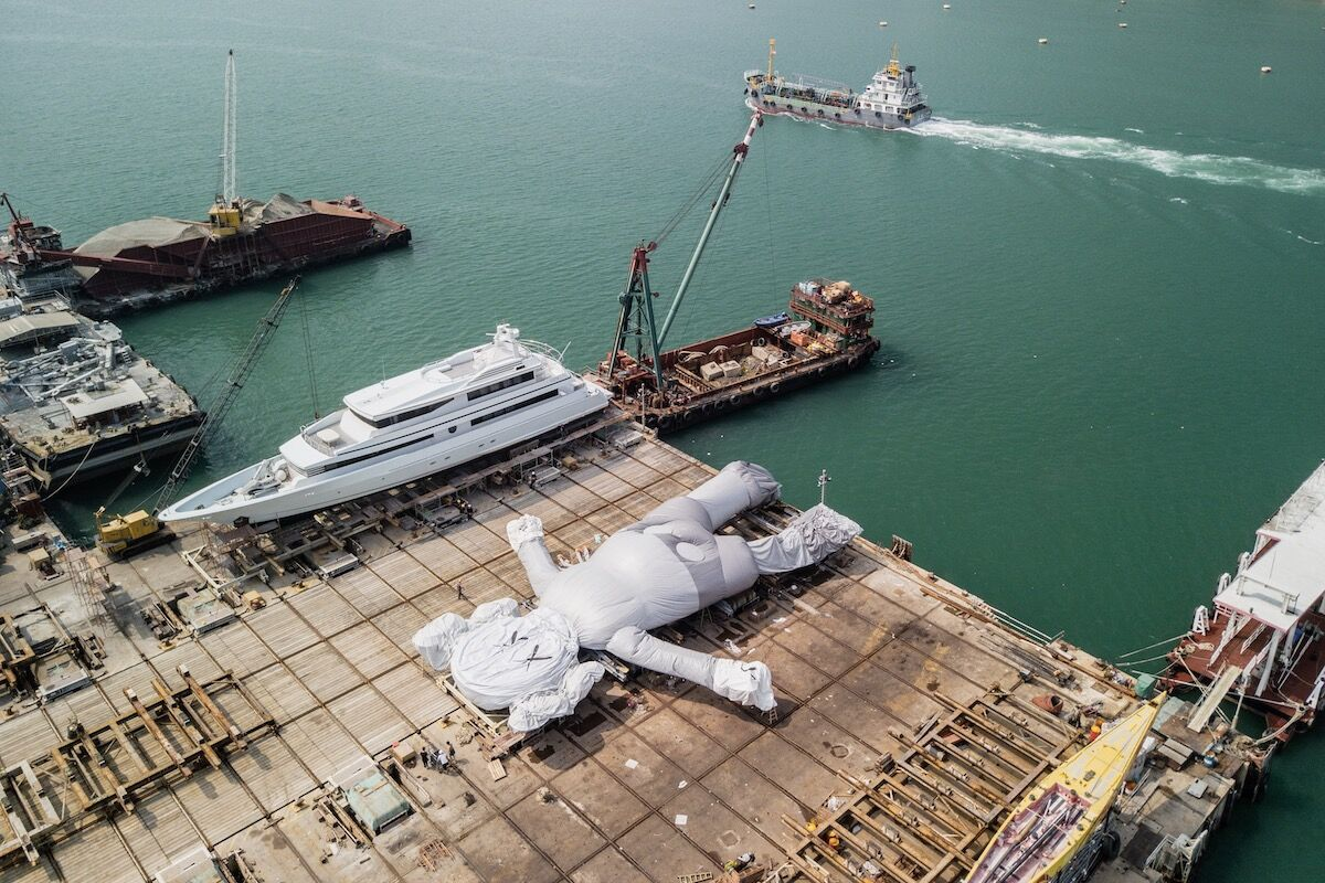 An inflatable KAWS sculpture in a shipyard in Hong Kong, where it will soon be installed in Victoria Harbour. Photo by Anthony Wallace/AFP/Getty Images.