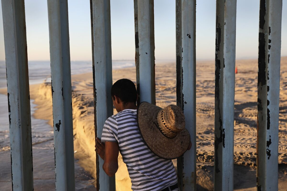 A man looks through the U.S.-Mexico border fence into the United States on September 25, 2016 in Tijuana, Mexico. Photo by John Moore/Getty Images. From Undocumented by John Moore, published by powerHouse Books.