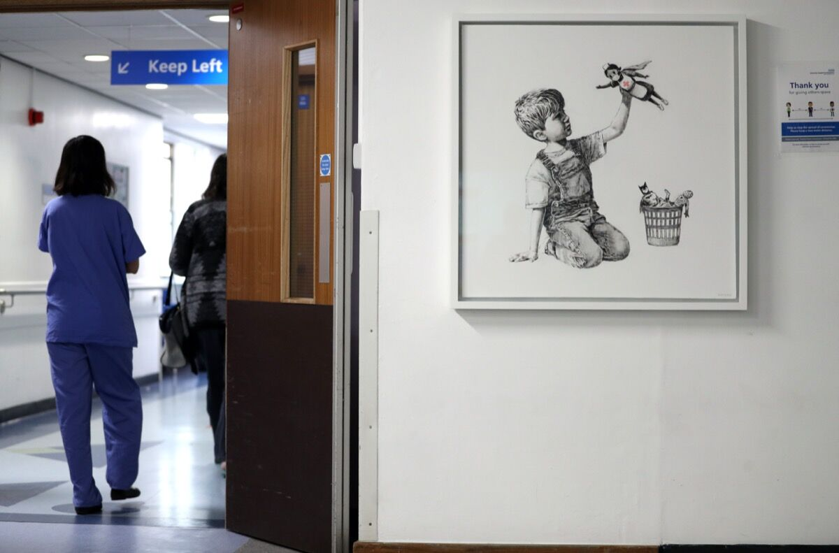 Installation view of Banksy's Game Changer, the new artwork painted during lockdown, which has gone on display to staff and patients on Level C of Southampton General Hospital. Photo by Andrew Matthews/PA Images. Image via Getty Images.