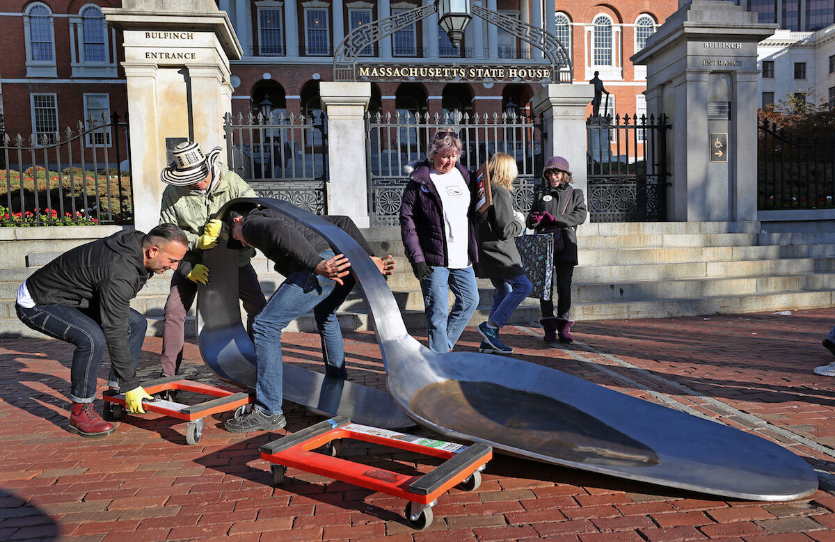 Chris Gromek uses his back to lift a stainless steel sculpture of a burnt heroin spoon weighing around 800 pounds with artist Domenic Esposito, left, and Spoon Movement gallery owner Fernando Alvarez, wearing hat, outside the Massachusetts State House in Boston on October 26, 2018. Photo by David L. Ryan/The Boston Globe via Getty Images.