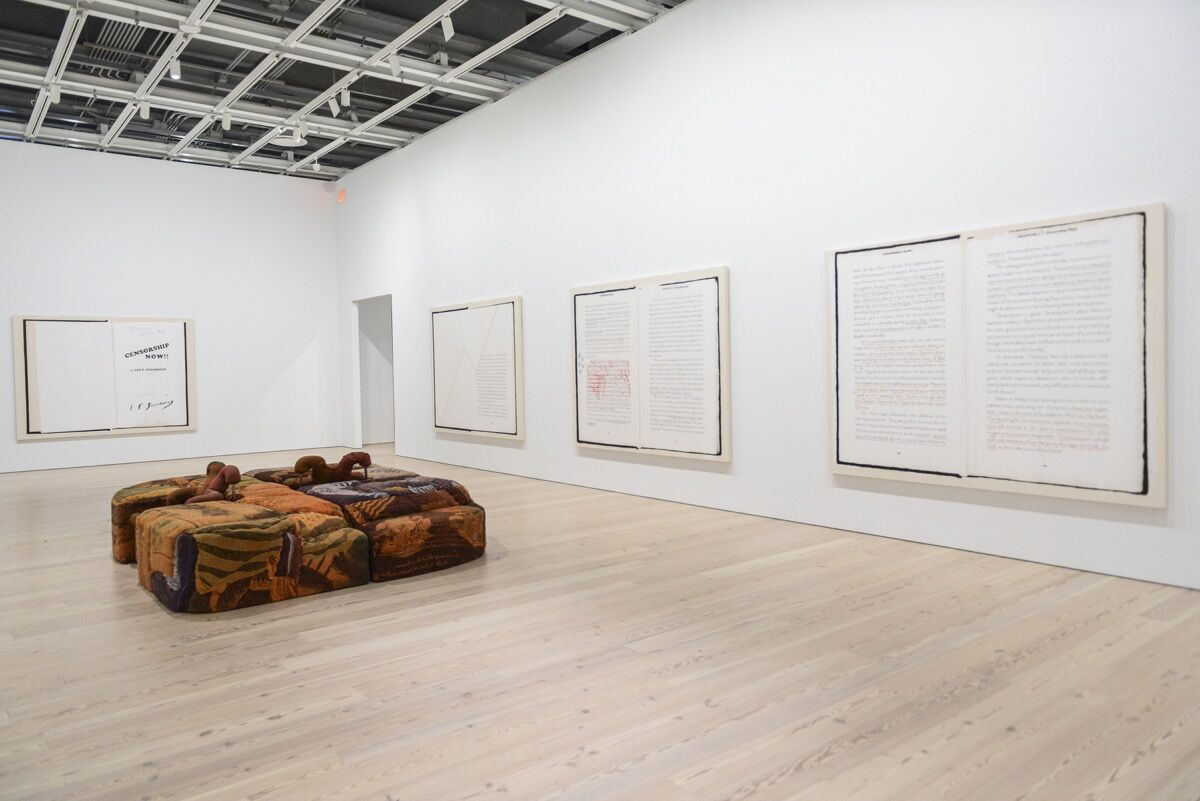 "Installation view of Jessi Reaves, Ottoman with Parked Chairs, 2017, and Frances Stark, Ian F. Svenonius's ""Censorship Now"" for the 2017 Whitney Biennial, 2017, at the 2017 Whitney Biennial. Photograph by Matthew Carasella, courtesy of the Whitney Museum of American Art."