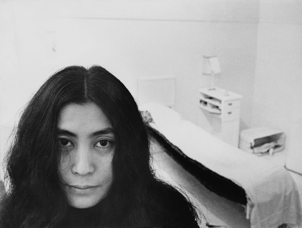 "Japanese artist and musician Yoko Ono sits in a white-painted half bedroom entitled Half-a-Room, in ""Half-a-Memory"" exhibition, at the Lisson Gallery, London, 1968. Photo by Roger Jones/Keystone Features/Getty Images."