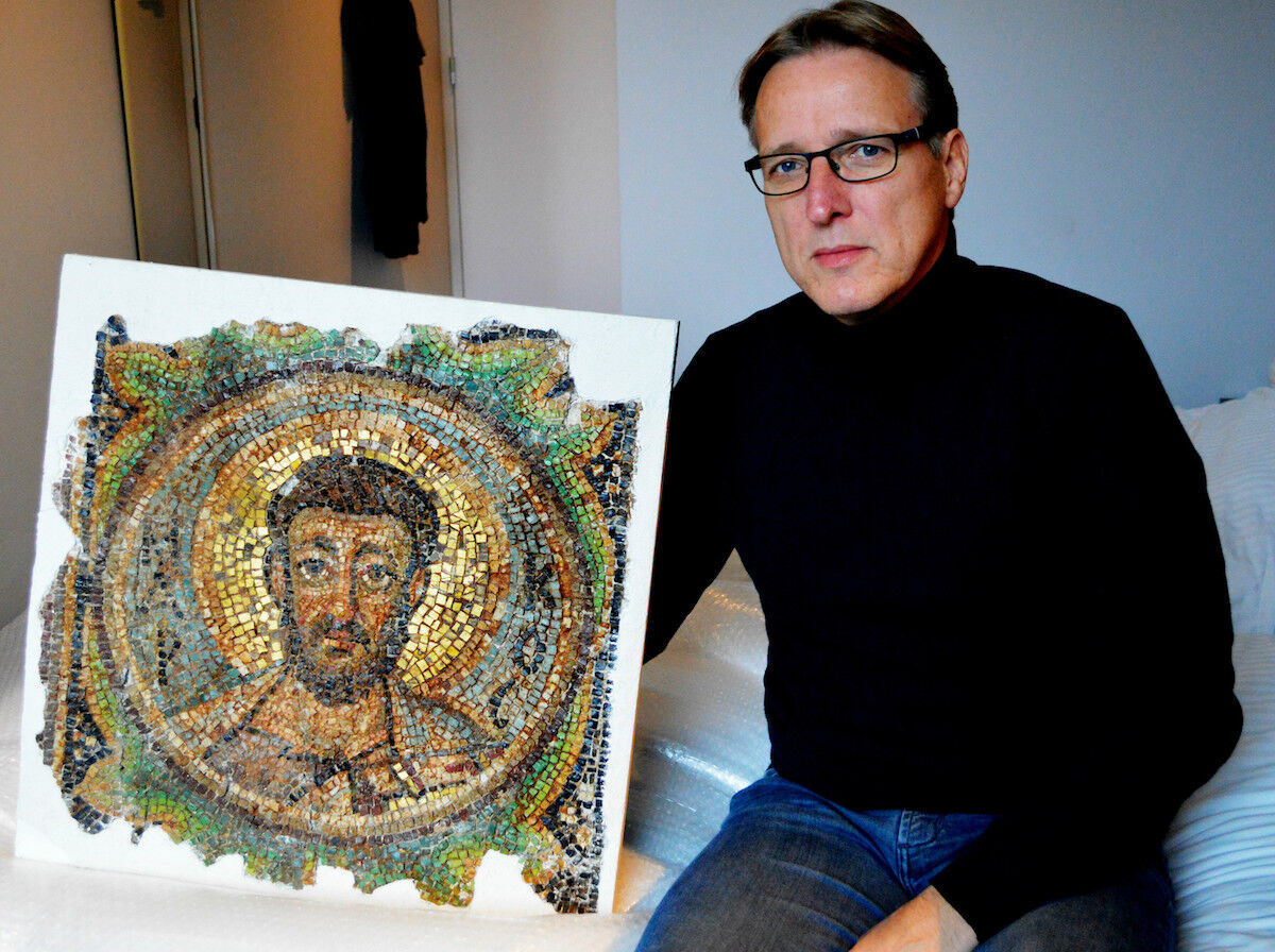 Dutch art detective Arthur Brand poses with the missing mosaic of Saint Mark, a rare piece of stolen Byzantine art from Cyprus, in a hotel room in The Hague. Photo by Jan Hennop/AFP/Getty Images.