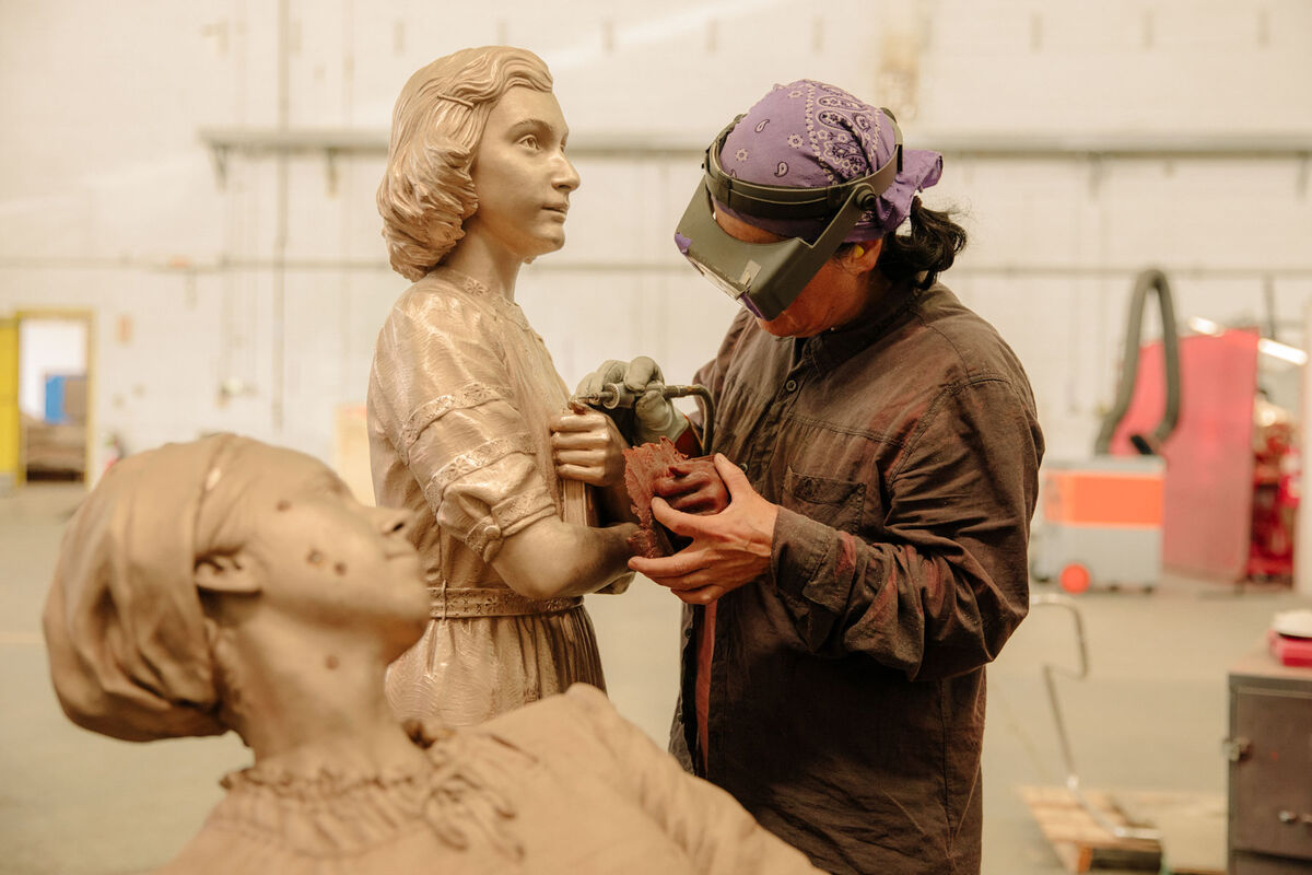 Metal finisher Insun Kim is refining details on a sculpture of Anne Frank for Studio EIS. Photo by Ricky Rhodes for Artsy.
