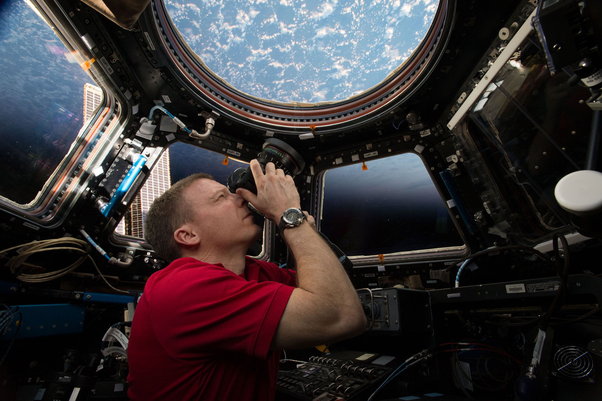 NASA astronaut and space photographer Terry Virts taking photos in the international space station's Cupola from the book View from Above, published by National Geographic, 2017. Courtesy of Terry Virts/NASA and National Geographic.