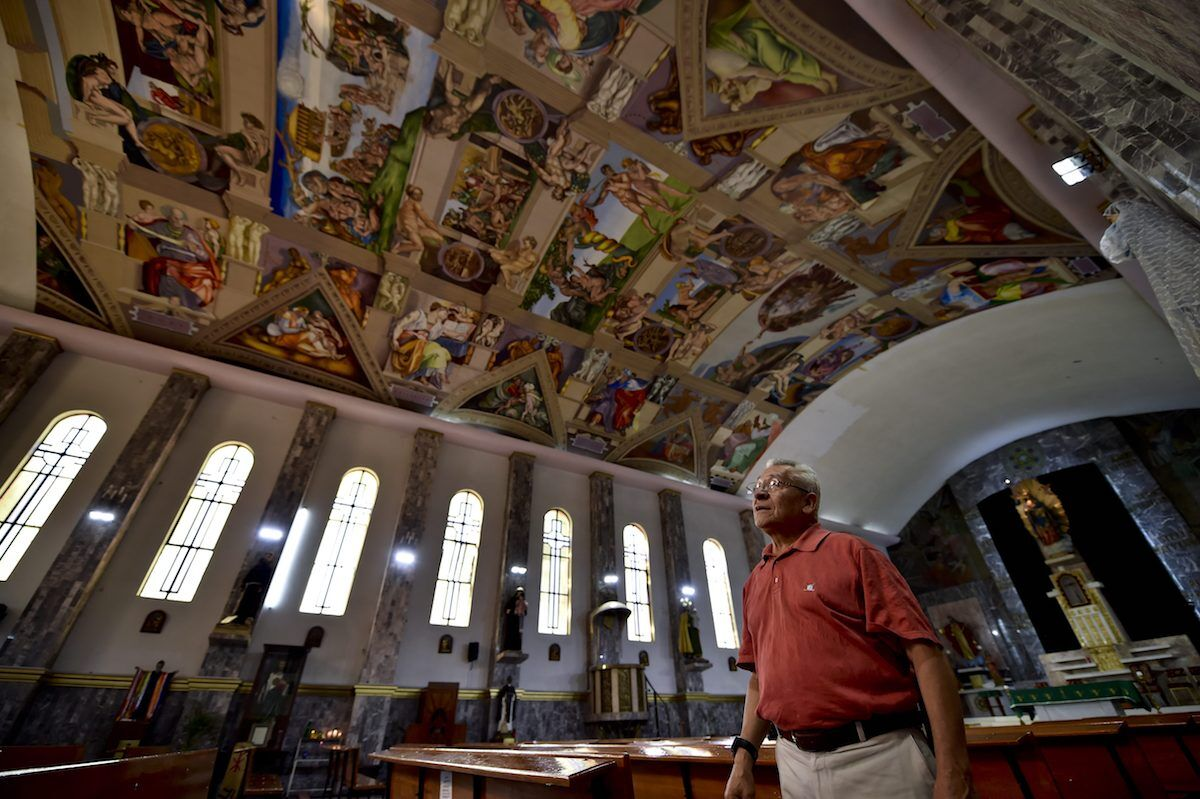Miguel Francisco Macías shows the of copies of original paintings by Michelangelo in the Sistine Chapel that he reproduced in the church of Nuestra Senora del Perpetuo Socorro. Photo by Yuri Cortez/AFP/Getty Images.