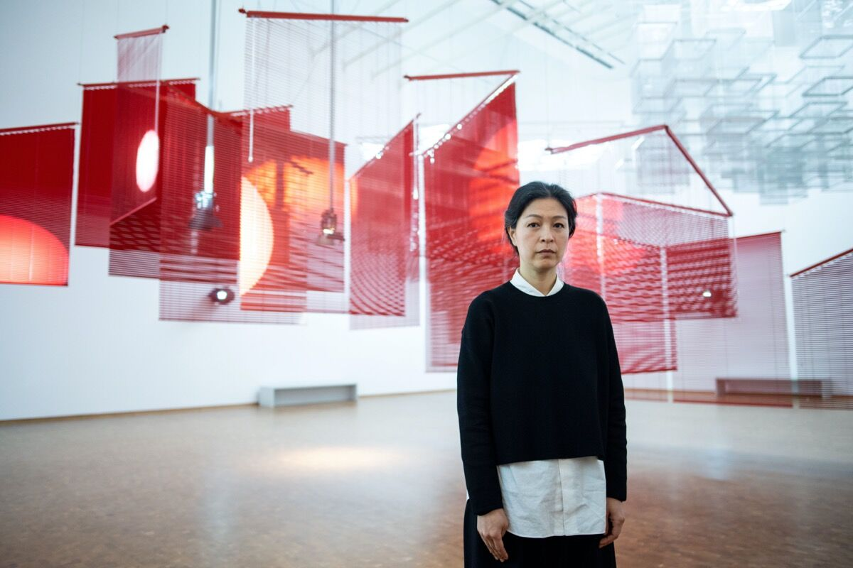 "Portrait of Haegue Yang in front of her installation Mountains of Encounter, 2008, in ""Haegue Yang: ETA 1994-2018"" at Museum Ludwig, 2018. Photo by Marius Becker. Image via Getty Images."