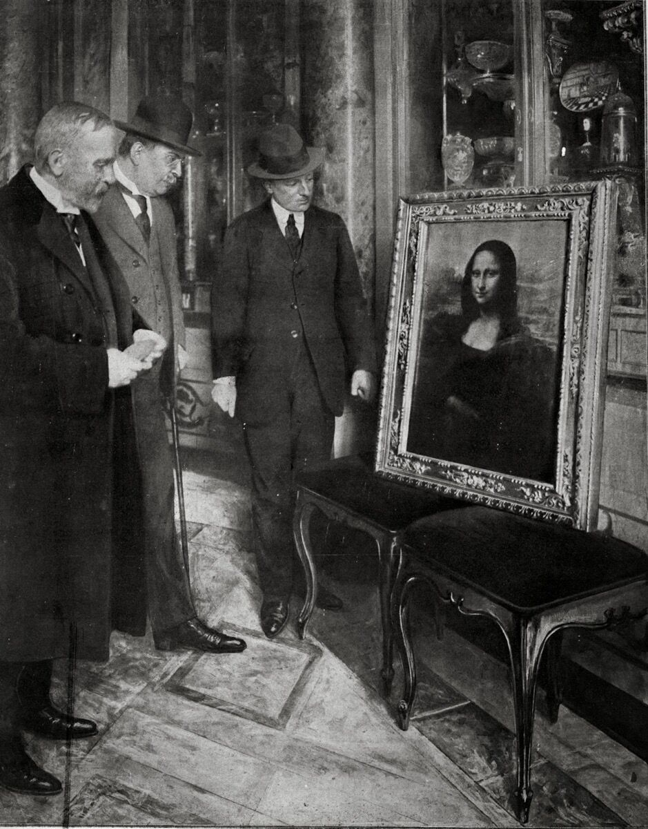 The Mona Lisa on display in the Uffizi Gallery, in Florence (Italy). Museum director Giovanni Poggi (right) inspects the painting. December 1913. Image via Wikimedia Commons.
