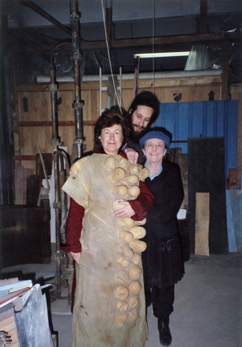 Portrait of Louise Bourgeois with Jerry Gorovoy and Ginny Williams (wearing a latex costume made by Bourgeois) at her Brooklyn Studio in 1991. © The Easton Foundation/Licensed by VAGA at Artists Rights Society (ARS), NY. Courtesy of Louise Bourgeois.
