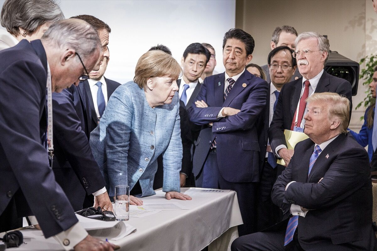 German Chancellor Angela Merkel deliberates with US president Donald Trump on the second day of the G7 summit on June 9, 2018  in Charlevoix, Canada. Photo by Jesco Denzel /Bundesregierung via Getty Images.