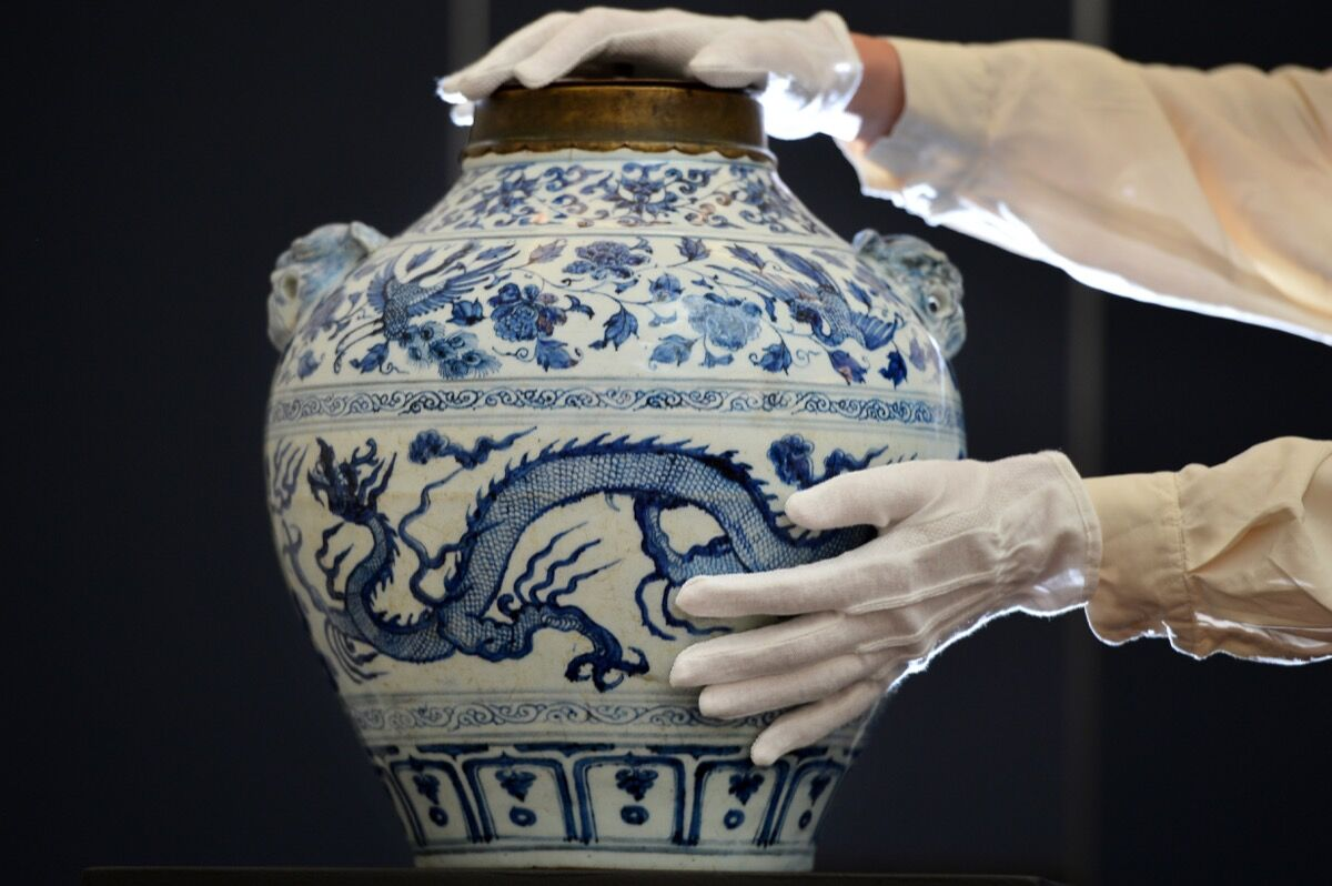 An Sotheby's employee poses with a Yuan dynasty blue and white 'Dragon and Phoenix' jar sold in Sotheby's Fine Chinese Ceramics and Works of Art auction in London on November 2, 2012.  Photo by BEN STANSALL/AFP/Getty Images.