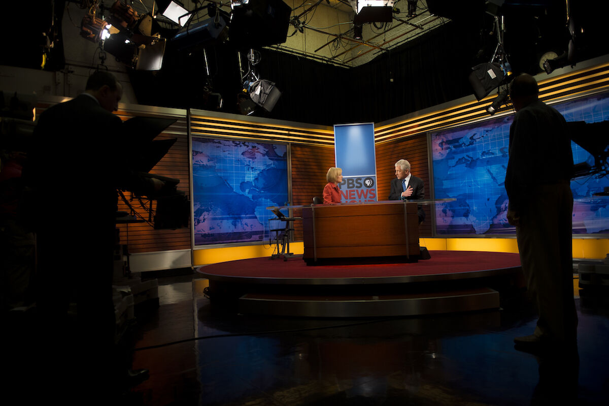 The set of PBS NewsHour during the filming of a segment in 2013. Department of Defense photo by Sgt. Aaron Hostutler, U.S. Marine Corps, via Wikimedia Commons.